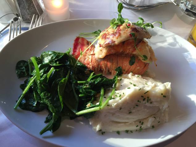 Oven baked lobster tail with crabmeat, mashed potatoes and sauteed spinach
